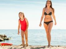 Ребенк маленькой девочки и мать женщины на пляже Стоковое фото RF