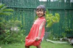 Ребенк наслаждаясь игрой с выплеском воды в саде стоковые фото