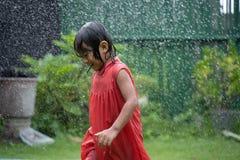 Ребенк наслаждаясь игрой с выплеском воды в саде стоковая фотография
