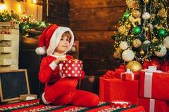 Ребенк носит одежды Санта, ждать Новый Год Концепция рождества Подарки на рождество Шляпа Санта стоковое изображение rf