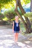 Ребенк подростка белокурый назад в школу Маленькая девочка ребенка с сумкой идет к начальной школе стоковое изображение rf