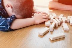 Ребенк потерял игру jenga Его башня от деревянных блоков упала Концепция риска и стратегии в деле и конструкции стоковые фото