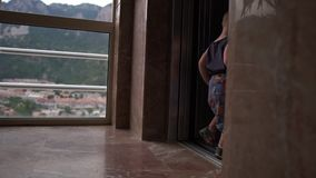 Ребенк пошел в лифт высотного здания на предпосылке гор видеоматериал