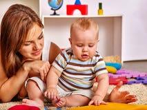 Ребенк при ребёнок матери играя с головоломкой забавляется на поле Стоковое Изображение RF