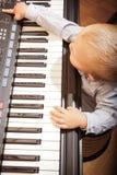 Ребенк ребенка мальчика играя на цифровом синтезаторе рояля клавиатуры стоковая фотография rf