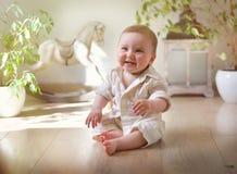Ребенк сидит на поле в светлой комнате Стоковая Фотография
