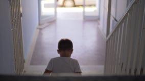 Ребенк сидя самостоятельно на лестницах