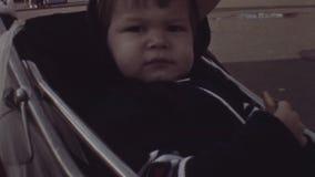 Ребенк старой винтажной цветной пленки маленький милый сидя в детской дорожной коляске держа печенье видеоматериал