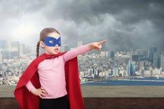 Ребенк супергероя против городской предпосылки и серого неба стоковое фото rf