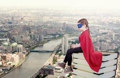 Ребенк супергероя сидя на стоге книг против городской предпосылки стоковые изображения