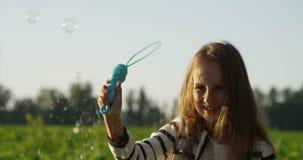 Ребенк с воздушными пузырями в поле играя и усмехаясь в замедленном движении акции видеоматериалы