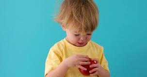 Ребенк с красно- очень вкусным яблоком на голубом backgroun видеоматериал