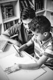 Ребенк школы порции учителя с его домашней работой в библиотеке стоковое фото rf
