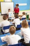 ребенокы школьного возраста класса изучая учителя Стоковая Фотография