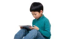 Ребенок Азии играя с таблеткой стоковое изображение