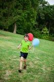 Ребенок бежать с воздушными шарами Стоковое Изображение