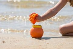 Ребенок брызгает влажный песок от прессформ в баке на seashore песчаного пляжа Стоковые Изображения