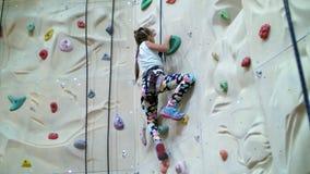 Ребенок взбирается на специальной стене для альпинизма девушка 7 лет в оборудовании для обеспечения безопасности приниманнсяый за видеоматериал