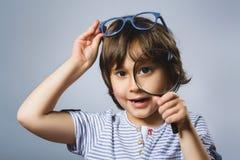 Ребенок видит до конца лупу, глаз ребенк смотря с объективом увеличителя над серым цветом Стоковая Фотография RF