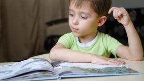 Ребенок внимательно читает книгу пока сидящ на таблице дома акции видеоматериалы