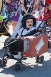 Ребенок выглядеть как Чарли Чаплин в шляпе и при зонтик и чемодан сидя в прогулочной коляске в параде prams в Volgo Стоковое Изображение