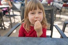 Ребенок в внешнем баре есть слойку сыра Стоковые Фотографии RF
