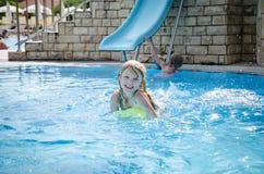 Ребенок в водных горках в бассейн стоковая фотография rf