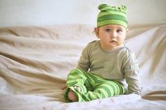 Ребенок в зеленой шляпе сидит на кровати Стоковые Фото