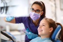 Ребенок в зубоврачебном стуле при женский дантист смотря зубоврачебную ногу стоковое фото