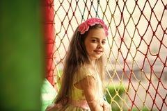 Ребенок в игровой Ребенок девушки с розовыми цветками в волосяной спиральной пружинке Стоковые Изображения