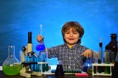 Ребенок в комнате класса с классн классным на предпосылке r Химия класс науки Маленькие ребята стоковые фото