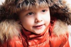 Ребенок в куртке меховой шапки и апельсина. стиль моды kid.children.close-up.winter Стоковая Фотография
