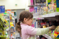 Ребенок в магазине игрушек выбирая приобретение Стоковые Фото