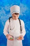 Ребенок в медицинском костюме держа пилюльки Стоковые Фотографии RF