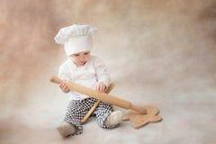 Ребенок, ребенок в поваре костюма шеф-повара с вращающей осью крыто стоковые изображения