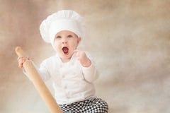 Ребенок, ребенок в поваре костюма шеф-повара с вращающей осью стоковые фотографии rf
