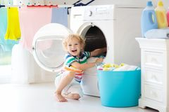 Ребенок в прачечной с стиральной машиной стоковое фото