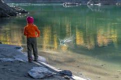 Ребенок, в теплых одеждах и камнях ходов красных крышки в воду от песочного берега стоковое фото
