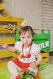 Ребенок в украинском национальном костюме с цыпленоком на ее голове Стоковая Фотография