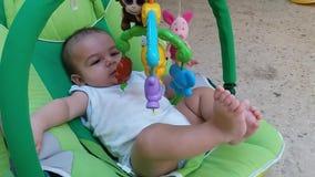 Ребенок в хвастуне кладя пальцы в его рот сток-видео