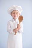 Ребенок в шеф-поваре костюма и крышки кашевар Стоковое Фото