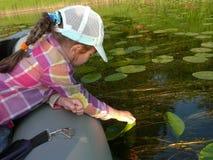 Ребенок в шлюпке на озере касается воде с его рукой стоковые изображения rf