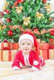 Ребенок в шляпе рождества против украшенной ели Стоковое фото RF
