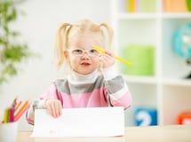 Ребенок в eyeglasses рисуя изображение дома Стоковая Фотография