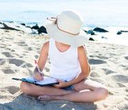 Ребенок девушка в шляпе пишет рисует мечты с песком на seashore Стоковая Фотография