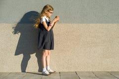 Ребенок девушки есть мороженое, стену предпосылки серую внешнюю, космос экземпляра Стоковые Изображения RF