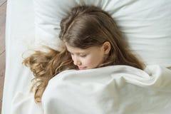 Ребенок девушки 7 лет старой блондинкы с длинными волнистыми волосами спать на подушке в кровати Стоковое Фото