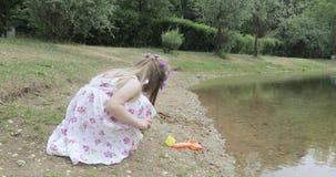 Ребенок девушки на береге пруда сток-видео