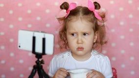 Ребенок девушки не хочет съесть еду Младенец наблюдая шарж на smartphone видеоматериал
