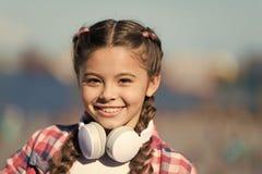 Ребенок девушки слушает музыка outdoors с современными наушниками Репертуар счета музыки подгоняет вашу музыку Открывать новый стоковые фото